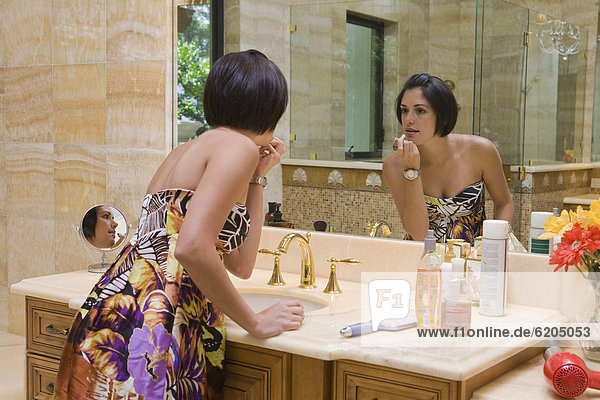 eincremen verteilen Frau Badezimmer Lippenstift Hispanier auftragen Spiegel