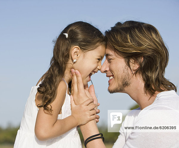Hispanic father and daughter smiling at one another