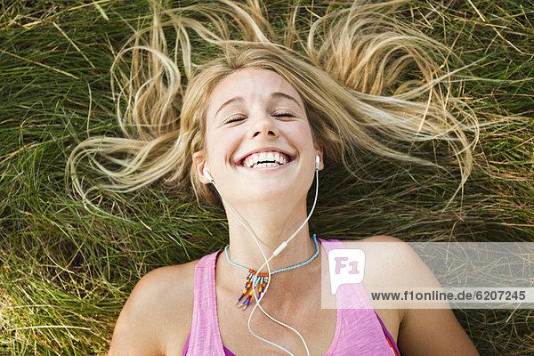 liegend  liegen  liegt  liegendes  liegender  liegende  daliegen  Europäer  Frau  zuhören  Musik  Gras