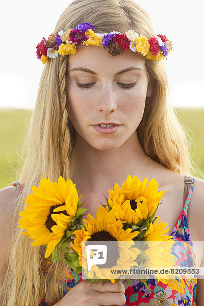 Tranquil Caucasian woman holding sunflowers