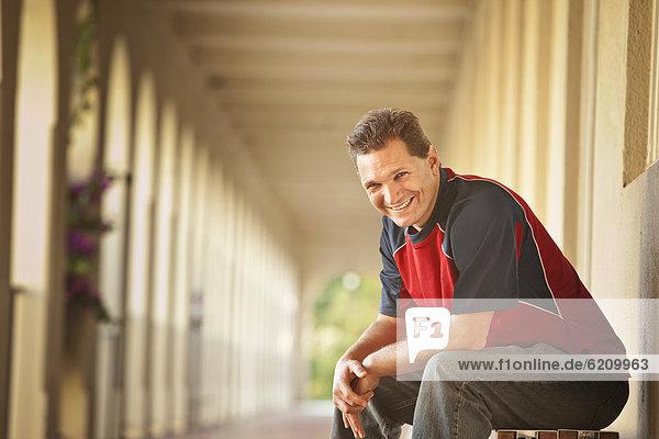 Außenaufnahme  sitzend  Europäer  Mann  lächeln  freie Natur Außenaufnahme ,sitzend ,Europäer ,Mann ,lächeln ,freie Natur