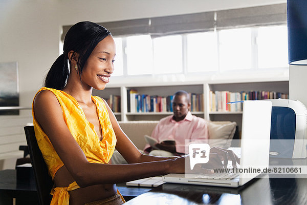 African couple reading and using laptop in living room
