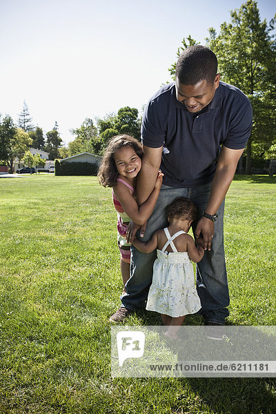 Father and daughters playing in park