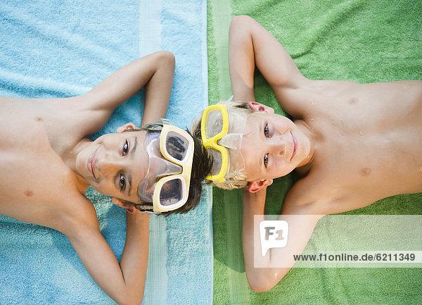 liegend  liegen  liegt  liegendes  liegender  liegende  daliegen  Junge - Person  Handtuch  Schutzbrille  Kleidung  schwimmen