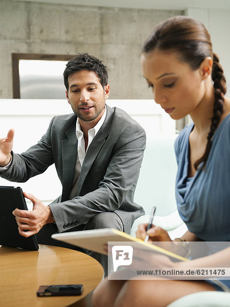Geschäftsmann und Geschäftsfrau arbeiten zusammen am Laptop in der Lobby
