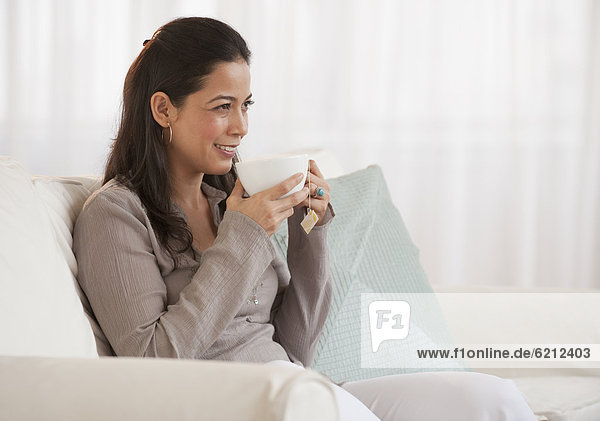 Hispanic woman drinking tea on sofa