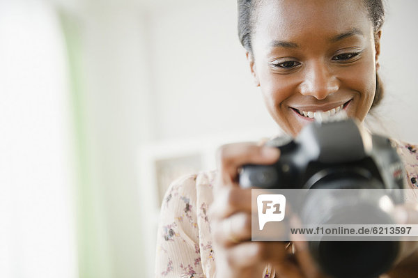 Black woman using digital SLR camera
