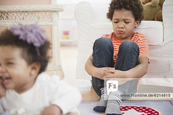 Sad Black boy sitting in living room