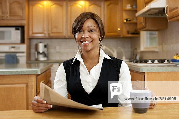 Frau  Küche  trinken  Kaffee  Zeitung  vorlesen