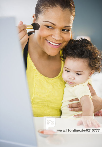 Mixed race other holding baby and putting on makeup
