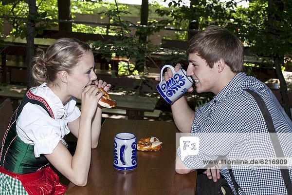 Junges Paar mit Dirndl und Lederhose sitzt im Biergarten  bei Pettstatt  Oberfranken  Bayern  Deutschland  Europa