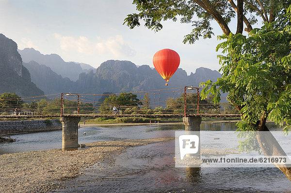 Ein Heißluftballon fliegt vor dem Karstgebirge  Vang Vieng  Laos  Südostasien