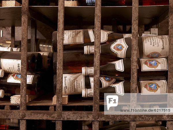 Verstaubte Weinflaschen älteren Jahrganges lagern hinter Gittern eines Weinkellers  Hattenheim  Rheingau  Hessen  Deutschland  Europa Verstaubte Weinflaschen älteren Jahrganges lagern hinter Gittern eines Weinkellers, Hattenheim, Rheingau, Hessen, Deutschland, Europa
