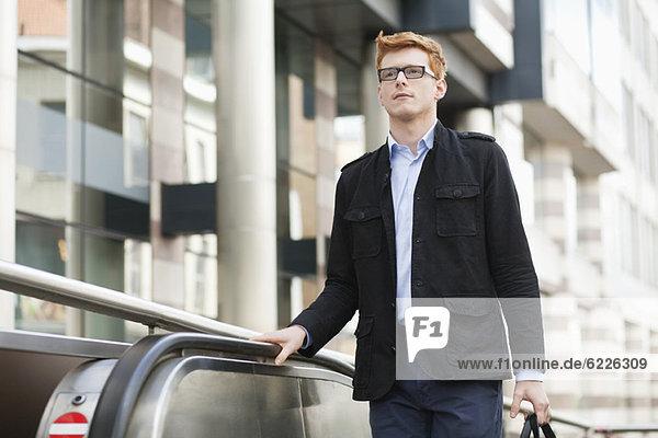 Businessman standing on escalator