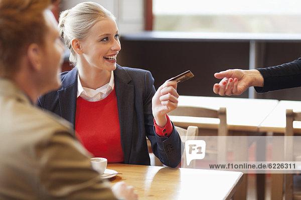 Frau bezahlt die Rechnung per Kreditkarte