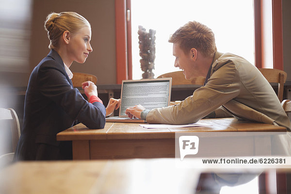 Business couple sitting in a restaurant using a laptop