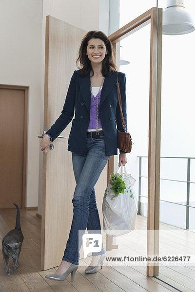 Frau  die mit einer Tüte Lebensmittel nach Hause kommt.