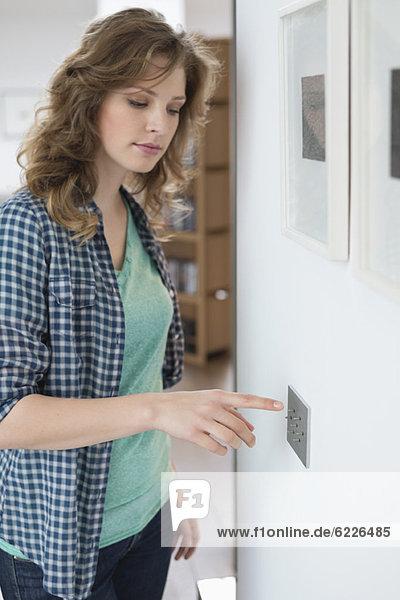 Frau drückt Lichtschalter an der Wand