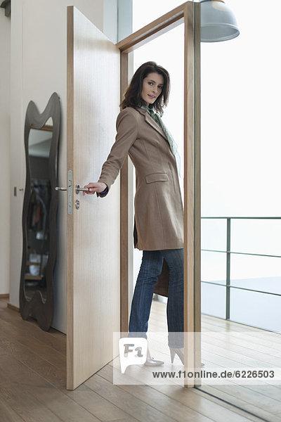 Frau  die die Tür eines Hauses schließt.