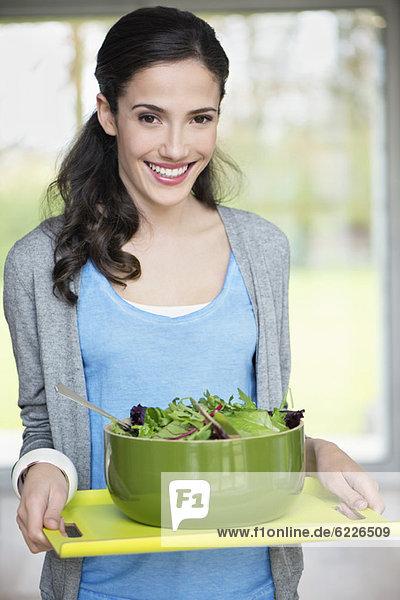Frau mit einer Schüssel Salat auf einem Tablett