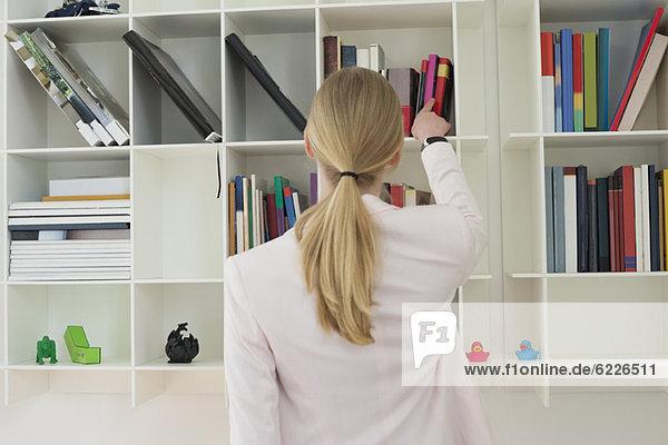 Frau beim Herausnehmen eines Buches aus dem Regal