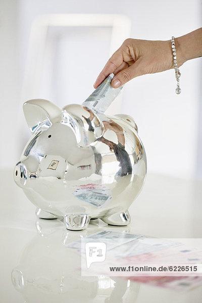 Die Hand einer Person  die Geld in ein Sparschwein steckt.
