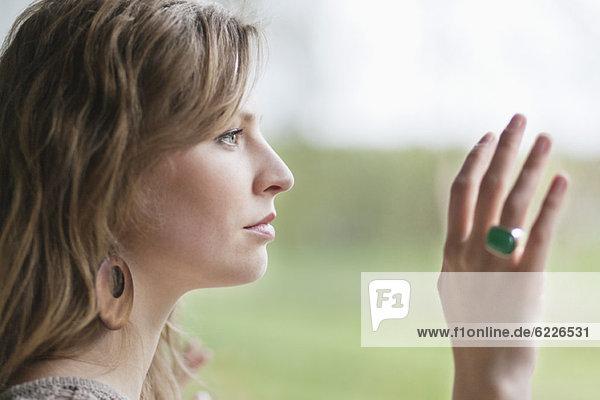 Nahaufnahme einer Frau  die durch das Glas eines Fensters schaut.