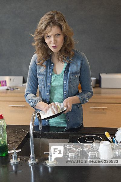Frau beim Geschirrspülen in der Küche