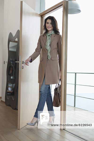 Frau öffnet die Tür eines Hauses