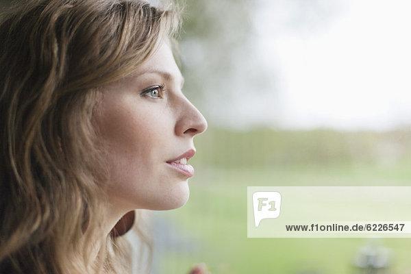 Nahaufnahme einer Frau beim Blick durchs Fenster