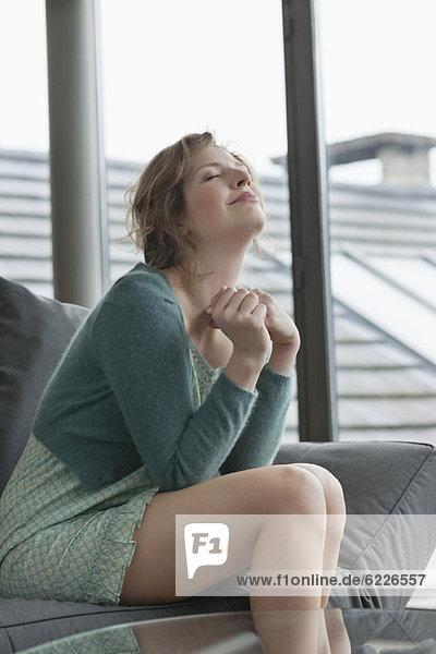 Frau sitzt mit geschlossenen Augen auf einer Couch.