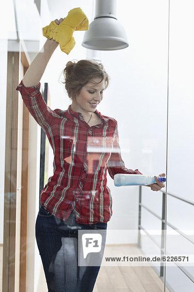 Frau reinigt Glastür