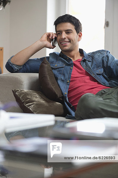 Man reclining on a couch and talking on a mobile phone