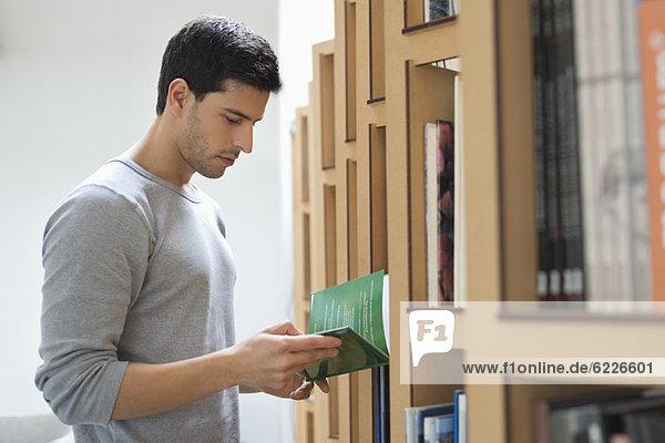 Mann  der ein Buch aus einem Bücherregal auswählt.