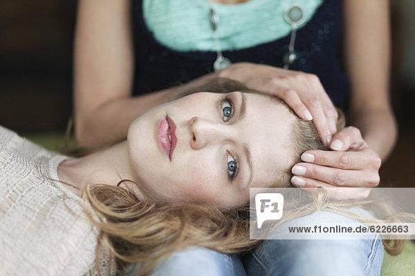 Frau auf dem Schoß ihrer Mutter liegend