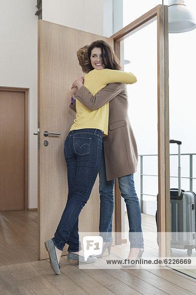 Frau begrüßt ihre Freundin am Eingang