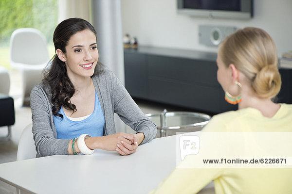Zwei Frauen sitzen sich am Tisch gegenüber.
