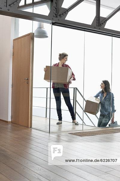 Zwei Freundinnen mit Pappkartons zu Hause