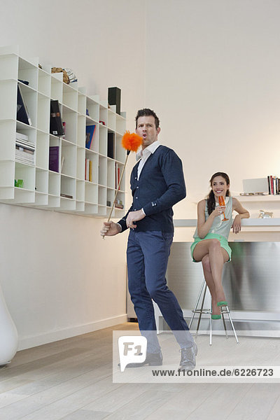 Man cleaning a bookshelf with his wife drinking champagne in the background