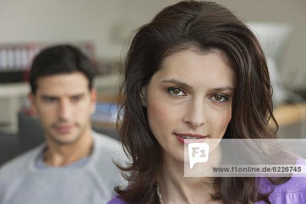 Porträt einer Frau  die mit ihrem Mann im Hintergrund lächelt