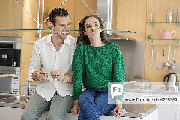 Pärchen spielen mit grünen Bohnen in der Küche