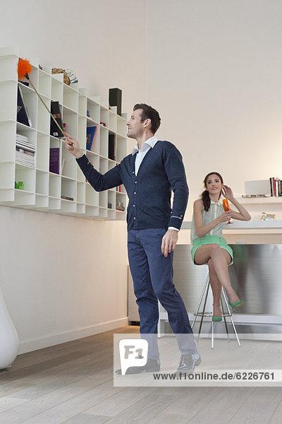 Mann putzt ein Bücherregal  seine Frau trinkt im Hintergrund Champagner.