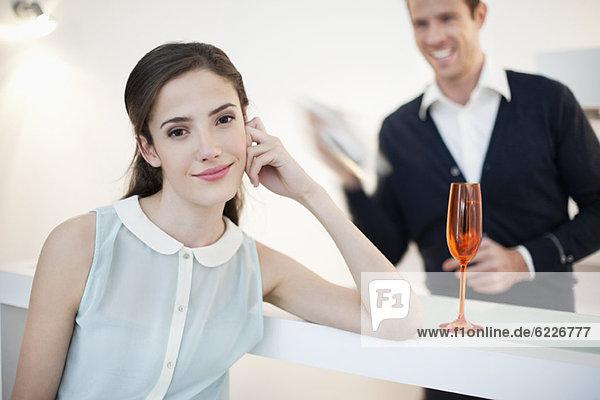 Frau lächelt mit ihrem Mann und schüttelt Cocktail im Hintergrund