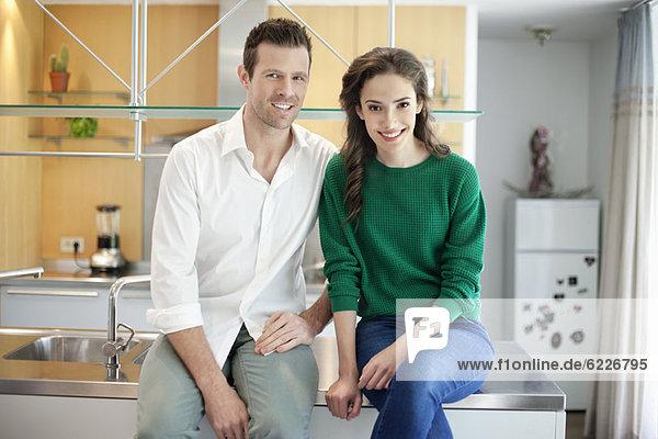 Paar auf der Küchenzeile sitzend und lächelnd