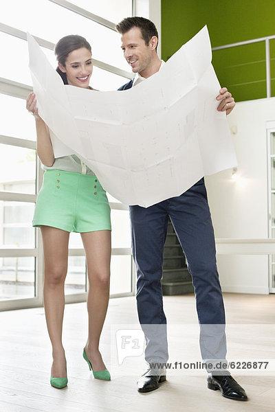 Ein Paar liest einen Bauplan in seinem neuen Zuhause.