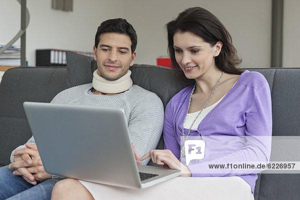 Frau benutzt einen Laptop mit ihrem Mann neben ihr.