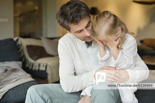 Mann hält seine süße Tochter  die ihre Augen mit den Händen bedeckt.
