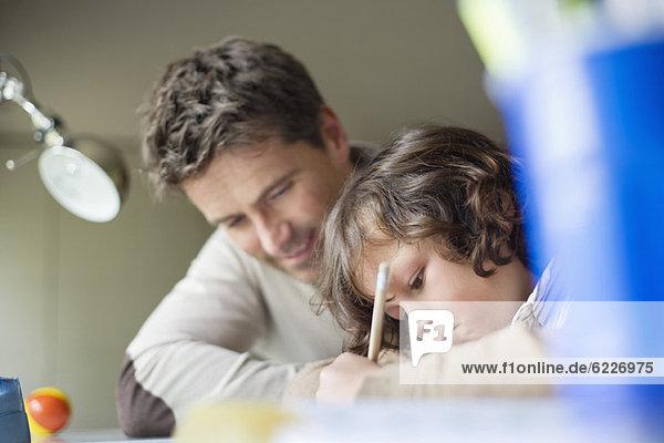 Junge studiert bei seinem Vater zu Hause