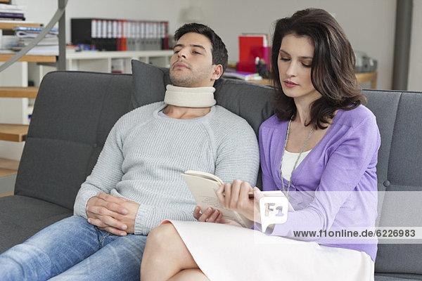 Frau liest ein Buch für ihren Mann  der an Nackenschmerzen leidet.