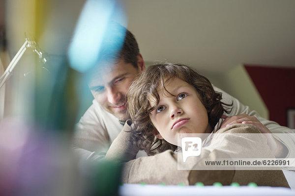 Junge denkt  während er bei seinem Vater zu Hause studiert.